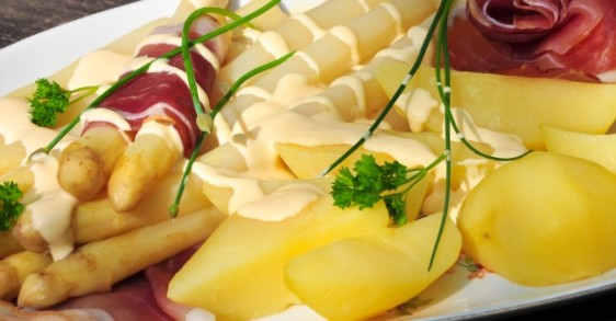 Asparagus accompanied with ham, potatoes and Hollandaise sauce